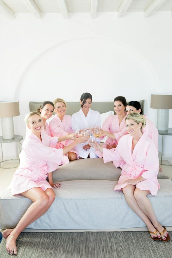 Bride with her bridesmaids wearing pink robes and drinking champagne at her preparation in Mykonos Greece before her wedding