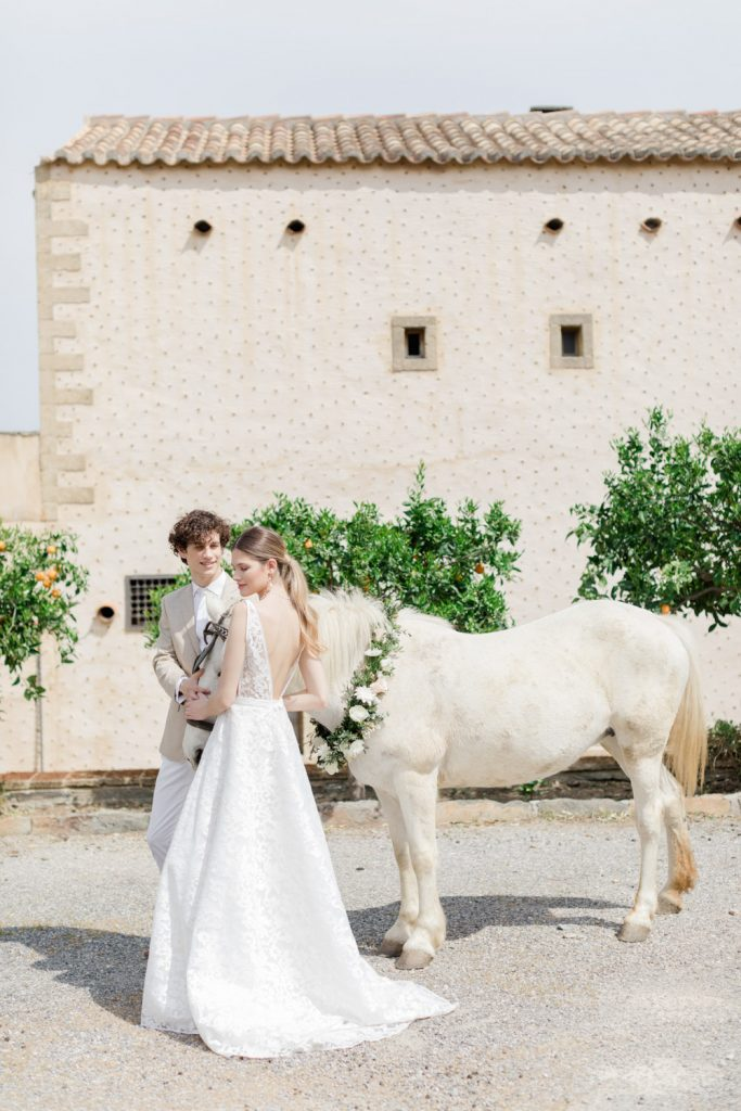 Couple's portrait with a white horse in kinsterna hotel wedding venue