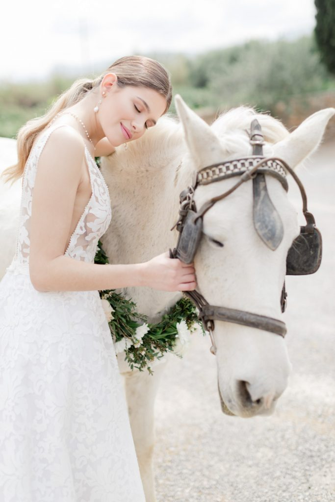 Portrait for the bride with a white horse after their wedding in Kinsterna hotel in Greece