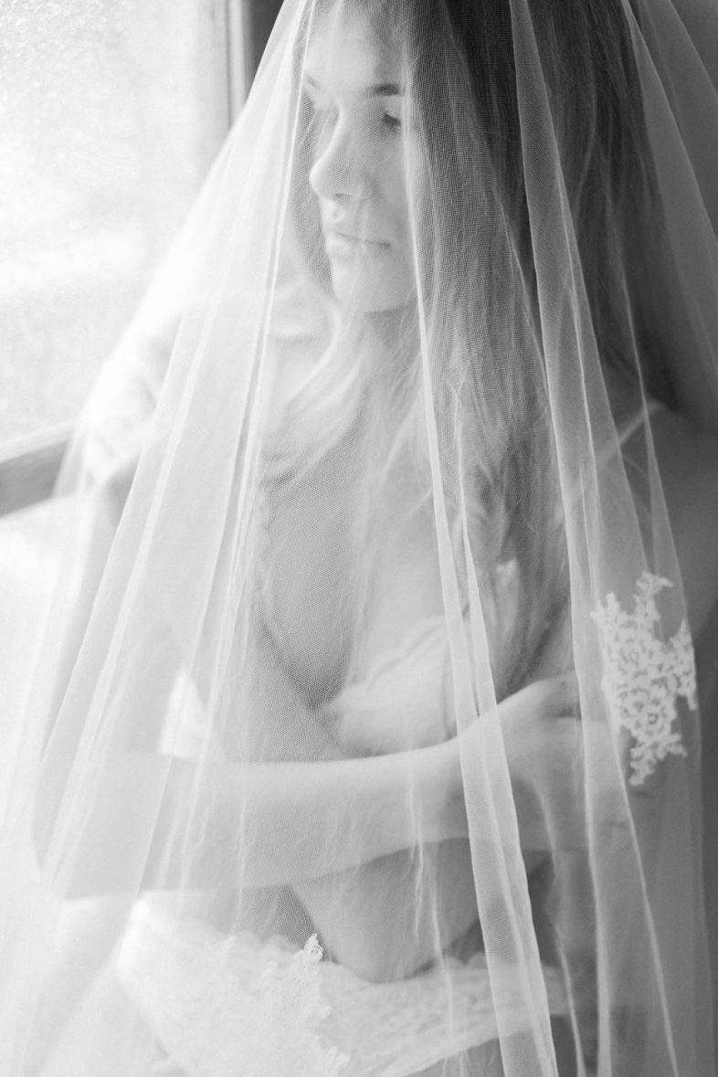 Bridal boudoir photographer in Greece - Bride is close by the window under her Veil which is made by Anemomilou wedding dress designer - Boudoir photographer Vasilis Kouroupis
