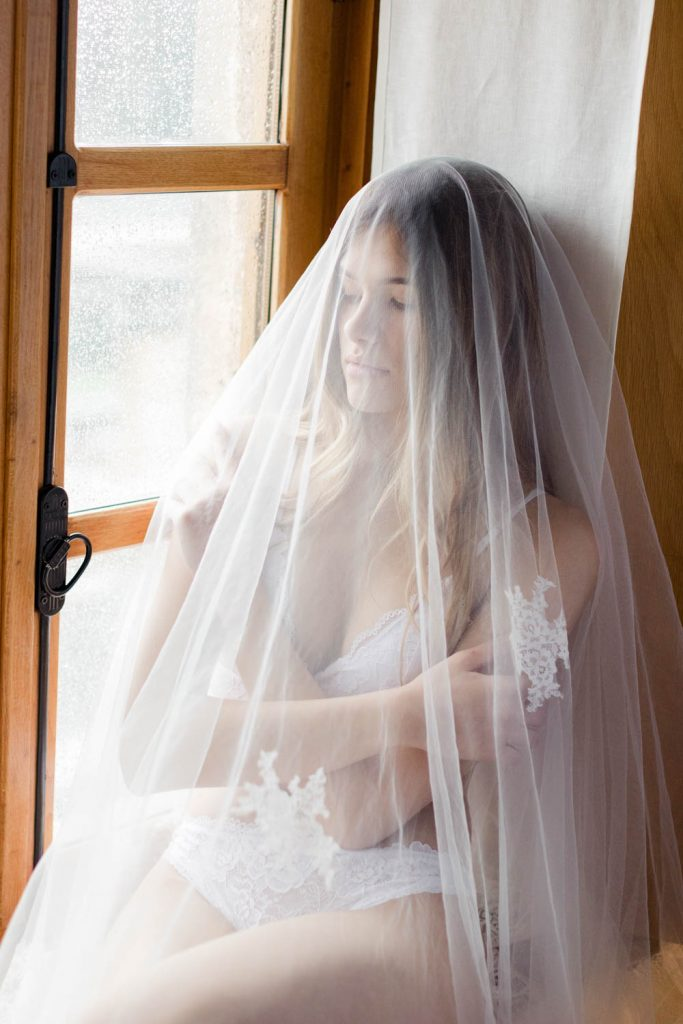 Bridal boudoir wedding photography in Greece - Bride is close by the window under her Veil which is made by Anemomilou wedding dress designer - Boudoir photographer Vasilis Kouroupis. Wedding planning dreams in style