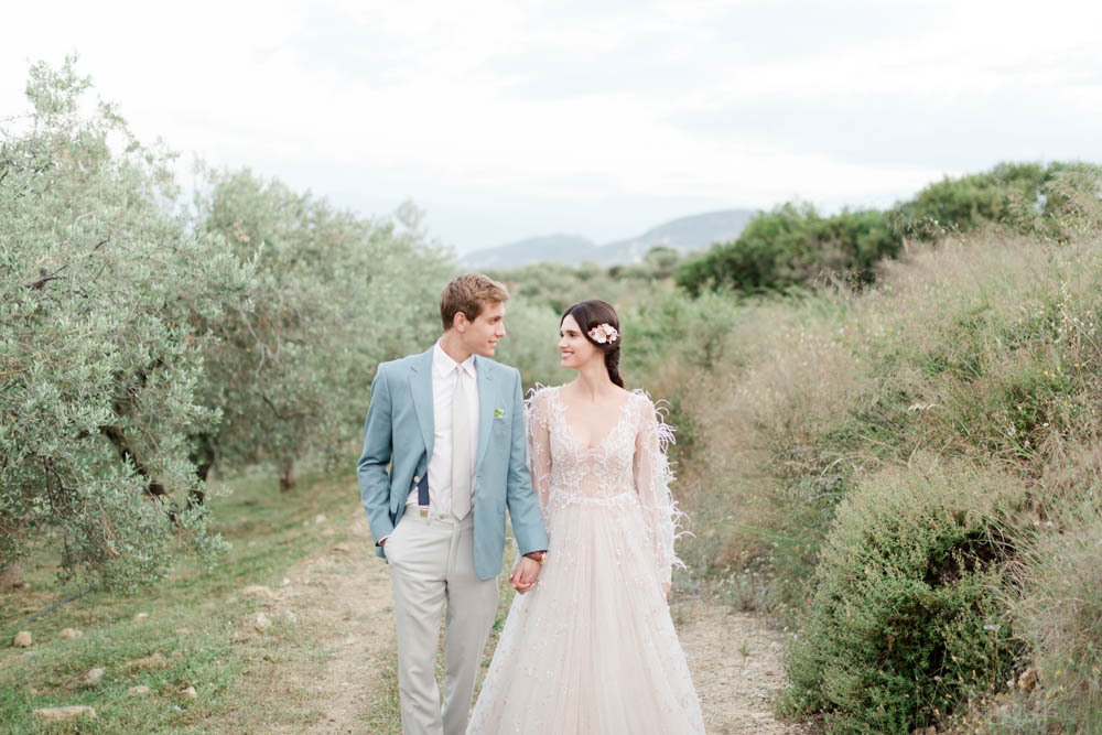 Wedding portrait into an olive garden, couple's portrait into green nature. Smiling talking and laughing. Organic wedding inspiration in Greece