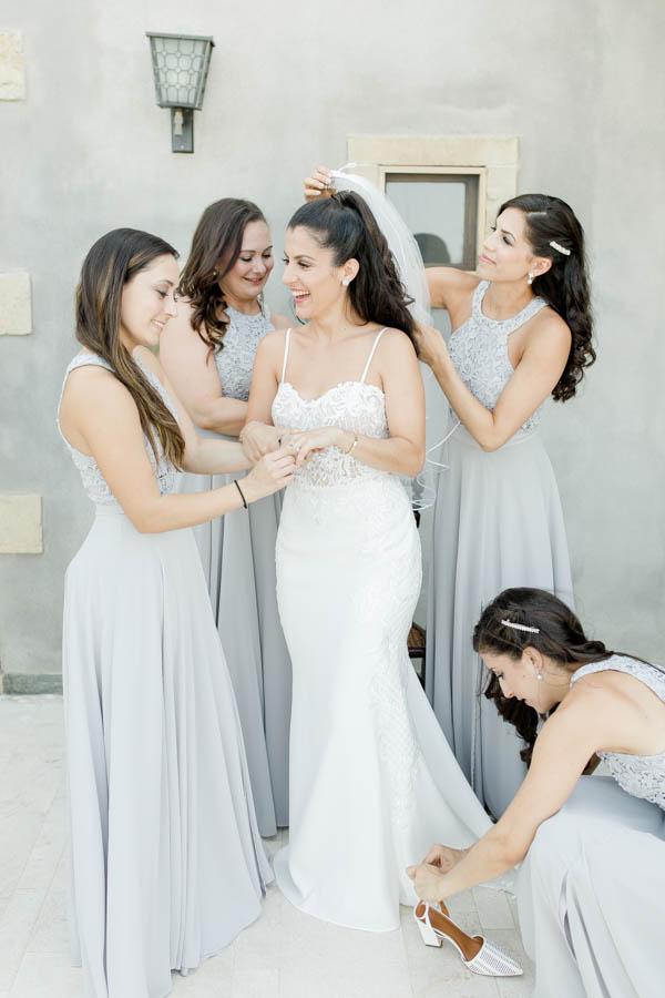 Bridesmaids helping bride on getting ready. Destination wedding in kinsterna hotel in monemvasia greece