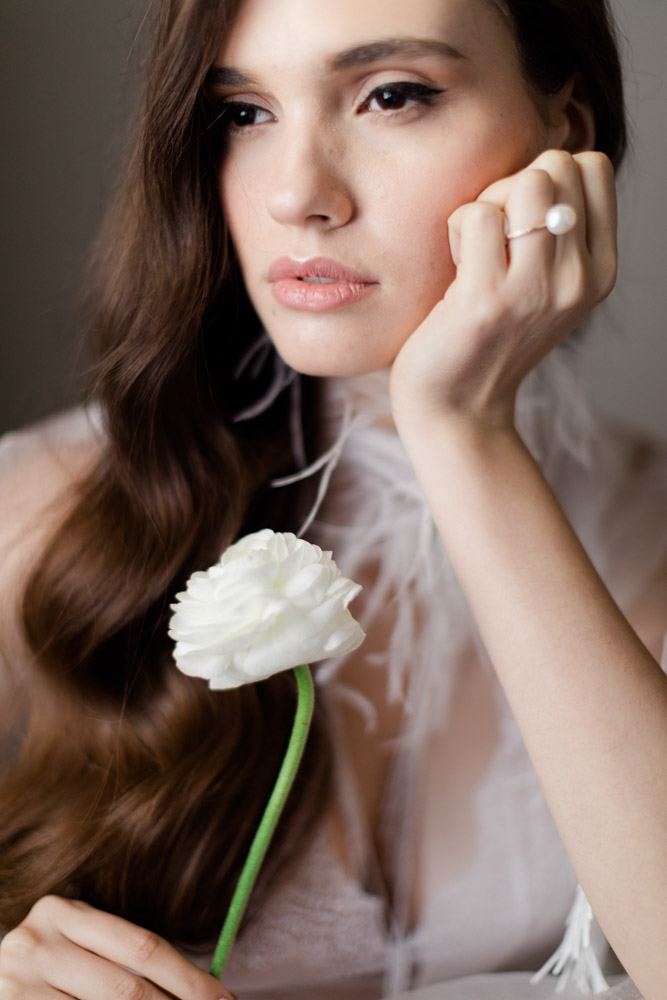 Elegant and classy bridal boudoir photography. Woman holding a white rose wearing her white lingerie. Wedding planning by think happy events planner