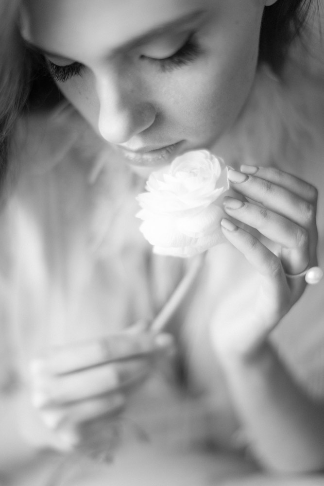 Woman smelling a white rose. Black and white bridal boudoir photography.